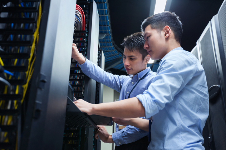Young IT Engineers Inspecting Data Center Servers